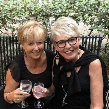Two smiling women hold wine glasses
