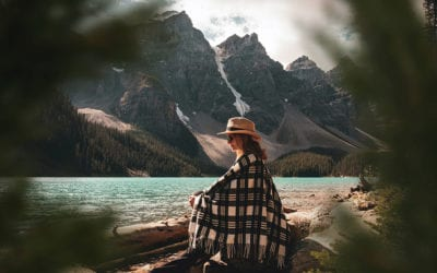 Older woman sits on a log wrapped in a blanket, mountains in the background