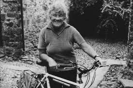 Black and white photo of Dervla Murphy with a bicycle