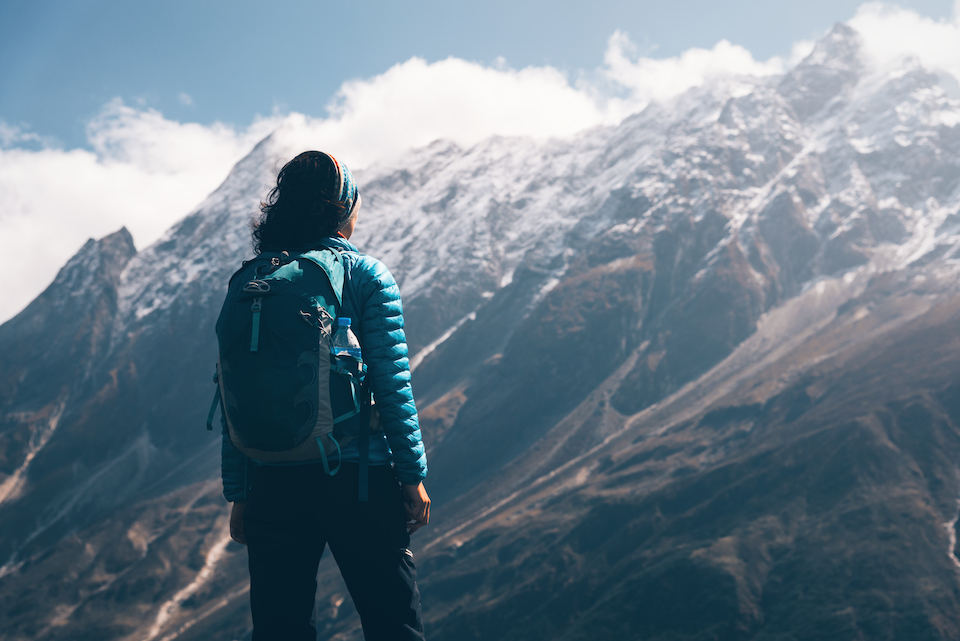 A woman holding a backpack, looking out into the mountains. Learn how to follow your travel dreams.